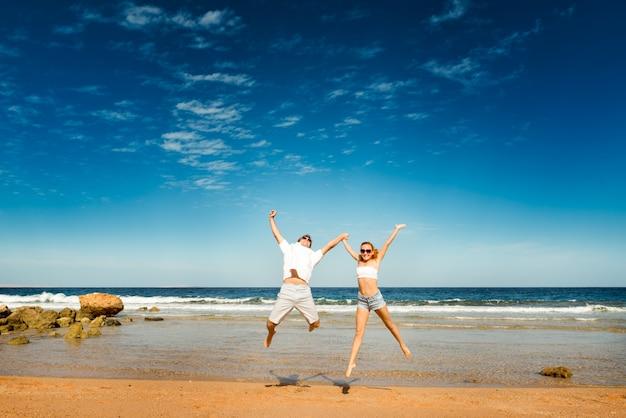 Glückliches paar am strand Kostenlose Fotos