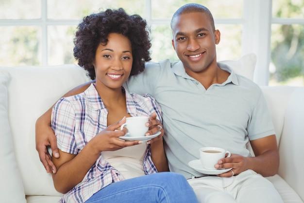 Glückliches paar auf dem sofa kaffee im wohnzimmer zu trinken Premium Fotos