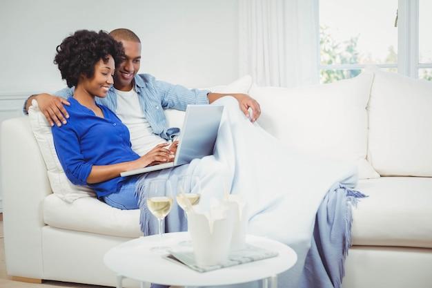 Glückliches paar auf dem sofa unter verwendung des laptops mit gläsern weißwein auf tabelle Premium Fotos