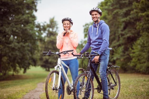 Glückliches paar auf einer fahrradfahrt in der landschaft Premium Fotos