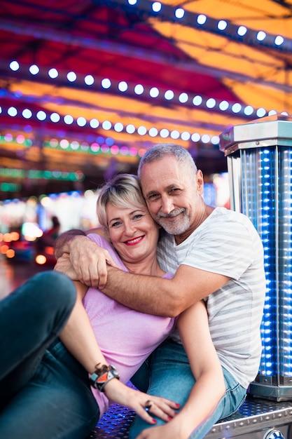 Glückliches paar, das am freizeitpark aufwirft Kostenlose Fotos