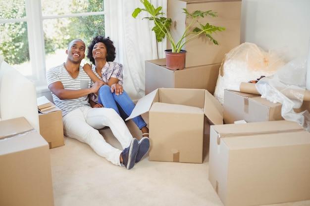 Glückliches paar, das auf dem boden im wohnzimmer sitzt Premium Fotos