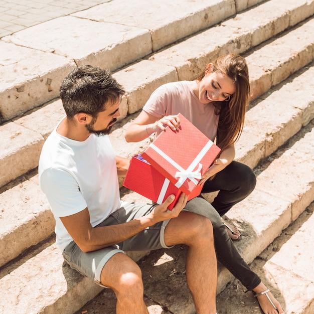 Glückliches paar, das auf dem treppenhaus öffnet rote geschenkbox sitzt Kostenlose Fotos