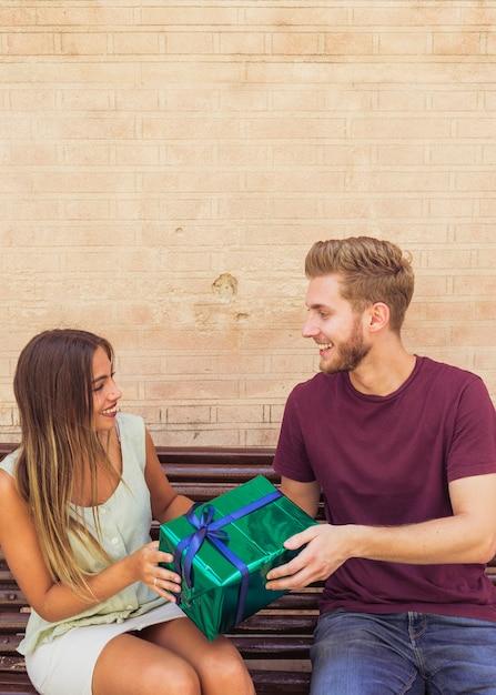 Glückliches paar, das auf der bank hält geschenk sitzt Kostenlose Fotos