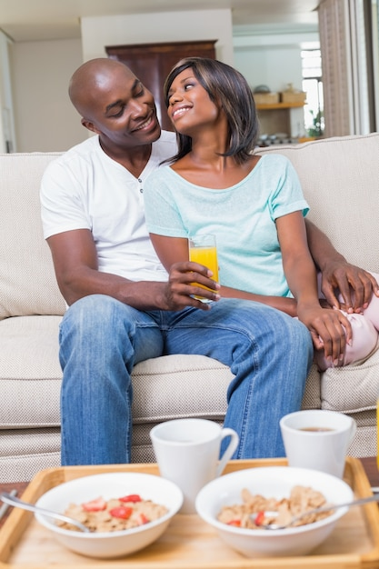 Glückliches paar, das auf der couch mit saft sich entspannt Premium Fotos