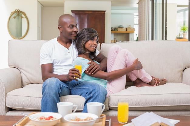 Glückliches paar, das auf der couch sich entspannt Premium Fotos