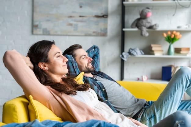 Glückliches paar, das auf der couch sitzt Kostenlose Fotos