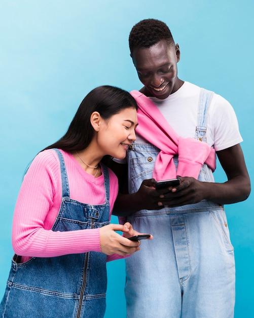 Glückliches paar, das auf smartphones schaut Kostenlose Fotos