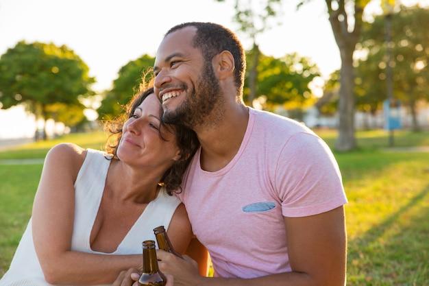 Glückliches paar, das datum im freien bei sonnenuntergang genießt Kostenlose Fotos