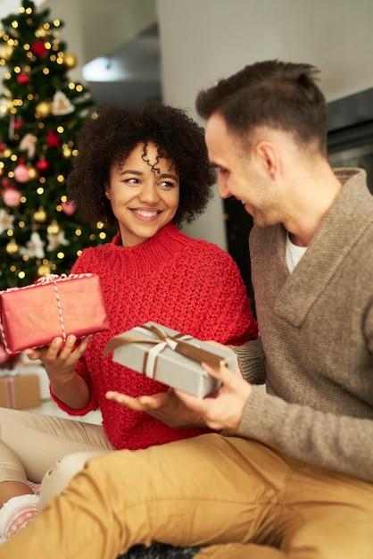 Glückliches paar, das die weihnachtsgeschenke teilt Kostenlose Fotos