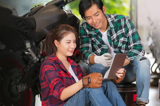 Glückliches paar, das digitale tablette an der reparatur und am kundenspezifischen motorradshop verwendet Premium Fotos