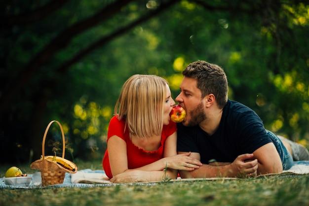 Glückliches paar, das draußen einen apfel isst Kostenlose Fotos