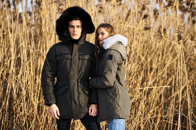 Glückliches paar, das draußen im winter umarmt und lacht. lebensstil Premium Fotos