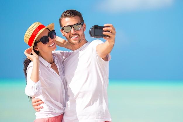 Glückliches paar, das ein foto auf weißem strand am flitterwochenfeiertag macht Premium Fotos