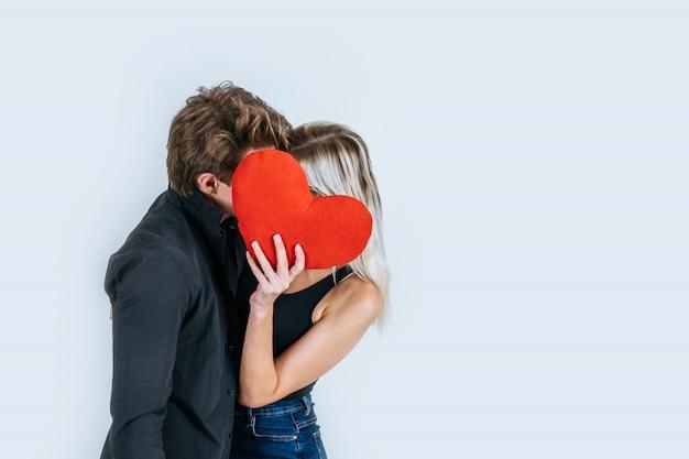 Glückliches paar, das ein rotes herz zusammenhalten liebt Kostenlose Fotos