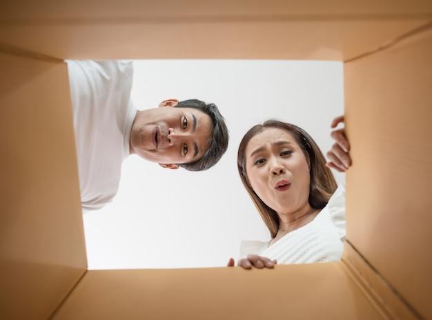 Glückliches paar, das einen kasten öffnet und nach innen zum produkt schaut Kostenlose Fotos