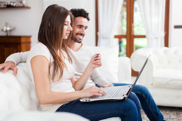 Glückliches paar, das einen laptop auf dem sofa verwendet Premium Fotos