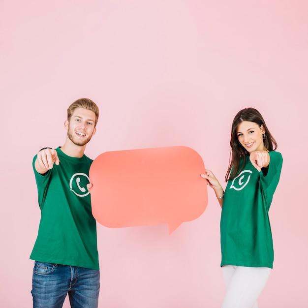 Glückliches paar, das finger beim halten der leeren orange spracheblase zeigt Kostenlose Fotos