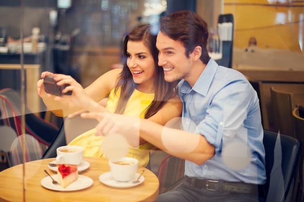 Glückliches paar, das foto im café macht Kostenlose Fotos