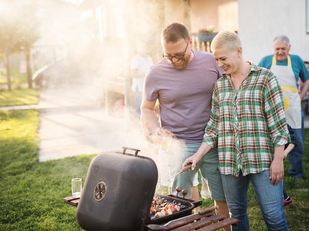 Glückliches paar, das grill für ihre familie in ihrem hinterhof macht. Premium Fotos