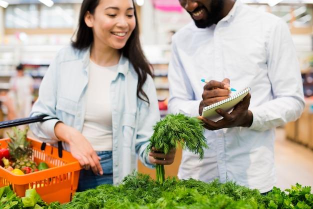 Glückliches paar, das grün im gemischtwarenladen wählt Kostenlose Fotos