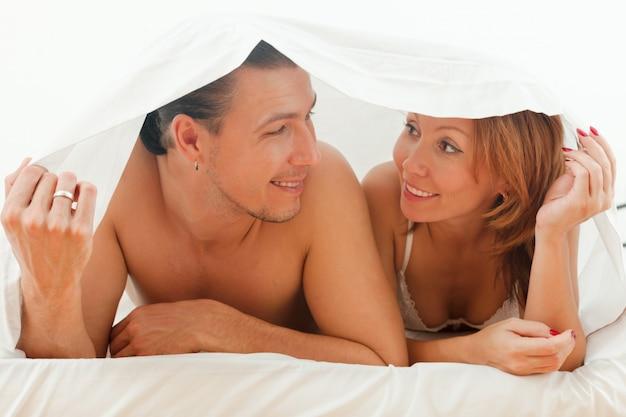 Glückliches paar, das im bett spielt Kostenlose Fotos