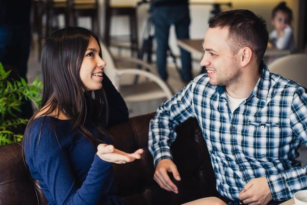 Glückliches paar, das im café spricht und tee trinkt Premium Fotos
