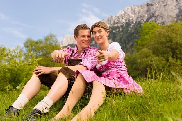 Glückliches paar, das in der alpenwiese sitzt Premium Fotos