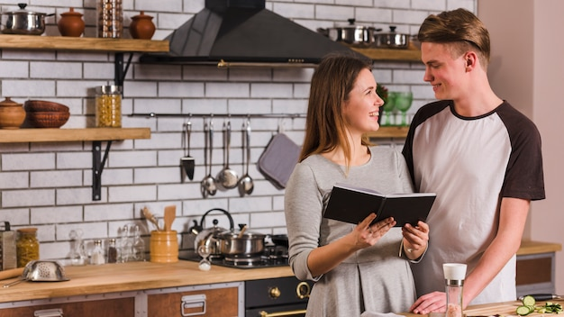 Glückliches paar, das in der küche mit notizbuch steht Kostenlose Fotos
