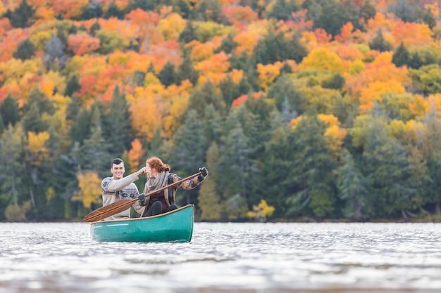 Glückliches paar, das in einem see in kanada canoeing ist Premium Fotos