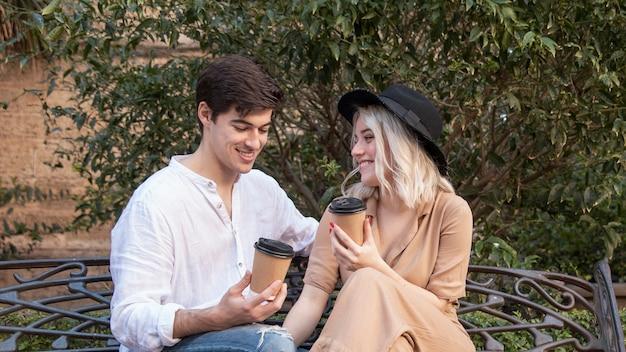 Glückliches paar, das kaffee auf der bank genießt Kostenlose Fotos