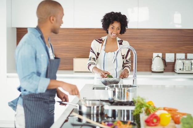 Glückliches paar, das mahlzeit in der küche vorbereitet Premium Fotos