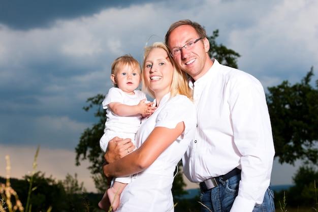 Glückliches paar, das mit ihrem baby in einem stürmischen wetter aufwirft Premium Fotos