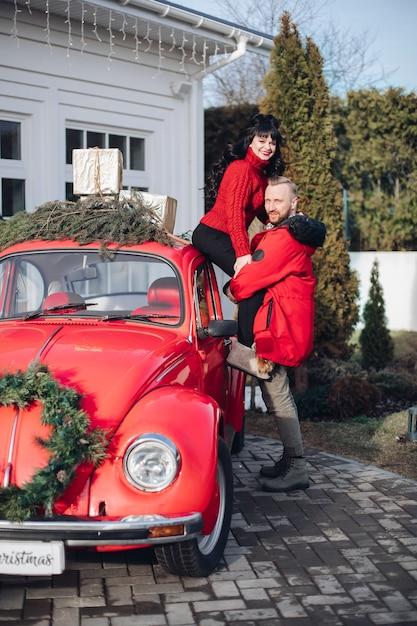 Glückliches paar, das mit rotem oldtimer aufwirft, verziert mit tannenzweigen und weihnachtsgeschenken. Kostenlose Fotos