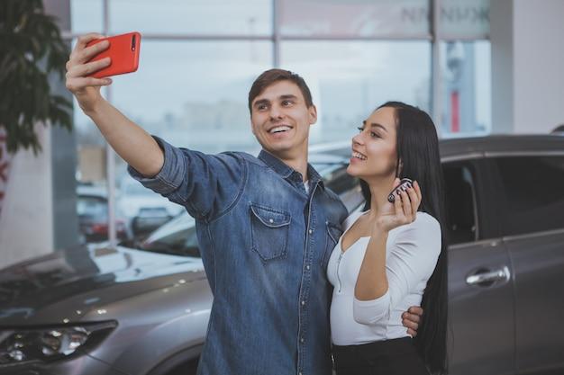 Glückliches paar, das neuwagen am verkaufsstellensalon kauft Premium Fotos