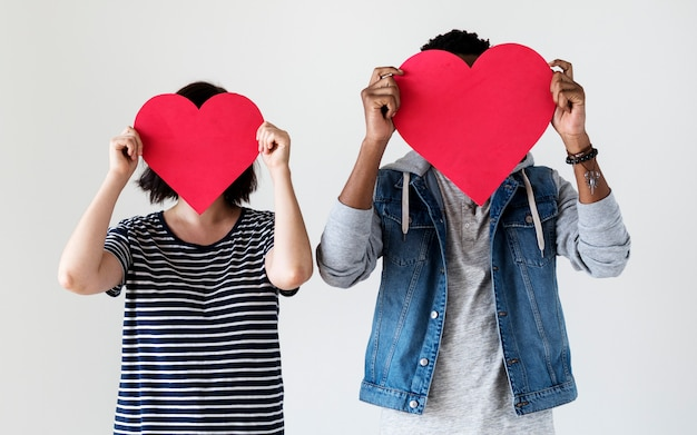 Glückliches paar, das rote herzikonen hält Kostenlose Fotos