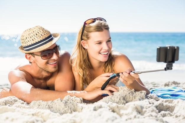 Glückliches paar, das selfie mit selfie stock nimmt Premium Fotos