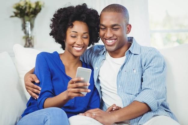Glückliches paar, das smartphone auf dem sofa verwendet Premium Fotos