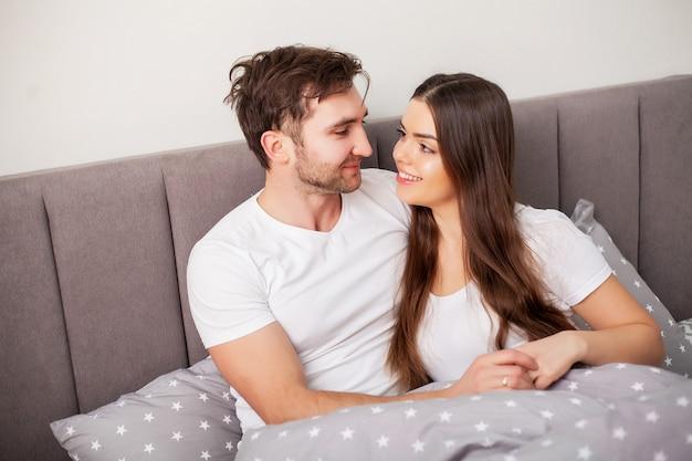 Glückliches paar, das spaß im bett hat. vertraute sinnliche junge paare im schlafzimmer, das sich amüsiert Premium Fotos