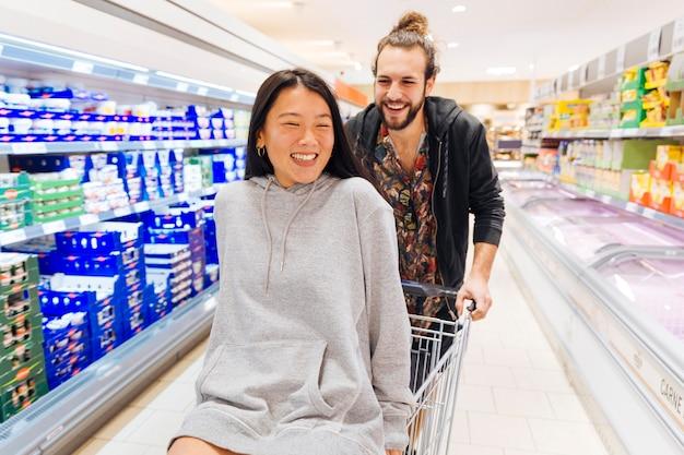 Glückliches paar, das spaß im supermarkt hat Kostenlose Fotos