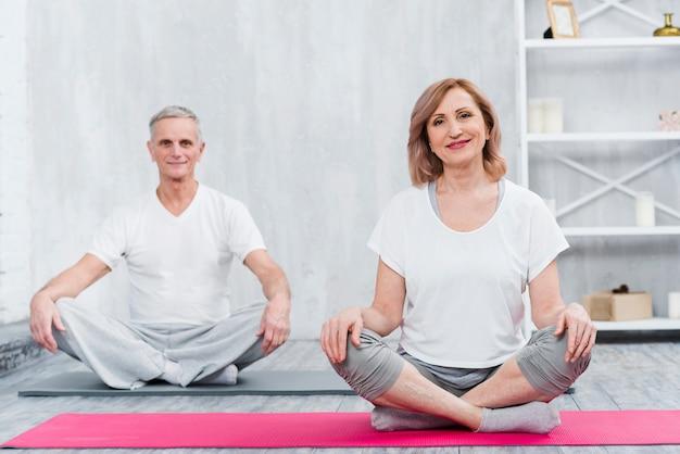 Glückliches paar, das zu hause auf yogamatte sitzt Kostenlose Fotos