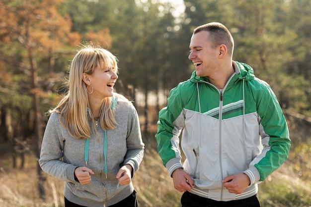 Glückliches paar, das zusammen in der natur läuft Kostenlose Fotos
