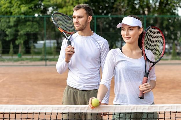 Glückliches paar der vorderansicht auf tennisplatz Kostenlose Fotos