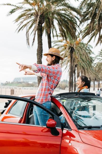 Glückliches paar im auto stehen Kostenlose Fotos