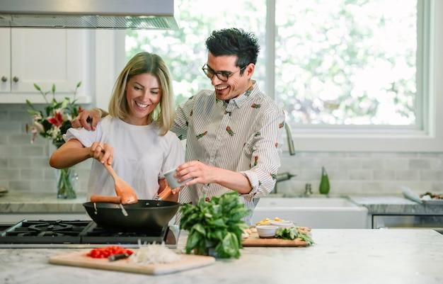 Glückliches paar in der küche kochen Premium Fotos