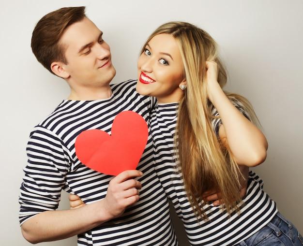 Glückliches paar in der liebe, die rotes herz hält. Premium Fotos
