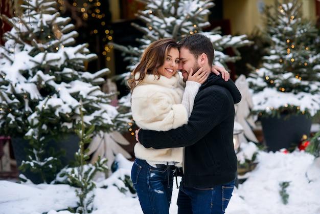 Glückliches paar in der warmen kleidung, die auf dem weihnachtsbaum mit lichtern sich umarmt. winterferien, weihnachten und neujahr. Premium Fotos