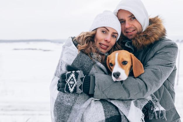 Glückliches paar in der winterlandschaft glückliche familie mit beagle-hund. wintersaison Premium Fotos