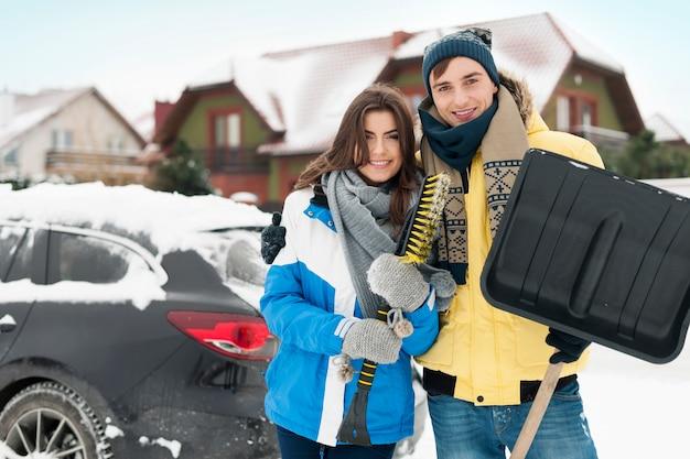 Glückliches paar ist bereit, auto vom schnee zu reinigen Kostenlose Fotos