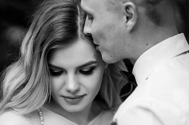 Glückliches paar. junge schöne braut und bräutigam mit einem hochzeitsstrauß Premium Fotos
